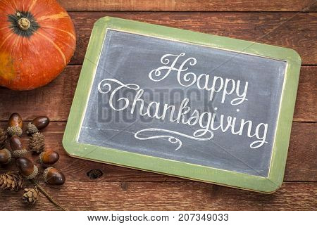 Happy Thanksgiving greeting card - white chalk text on a  vintage slate blackboard with winter squash and acorn