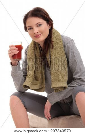 Young woman resting drinking juice after workout.