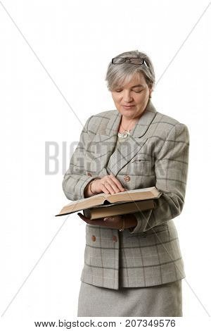 Mature female teacher reading book, isolated on white background.