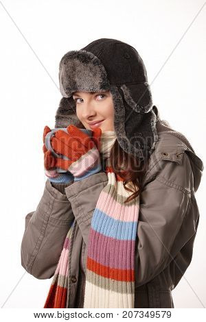 Young woman in warm outdoor clothing drinking tea, looking at camera, smiling, white background.