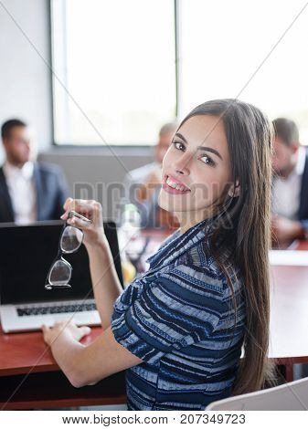 Bautiful office worker in blue dress smiling and posing on camera in the office. Cute brunette using laptop for work. Business concept.