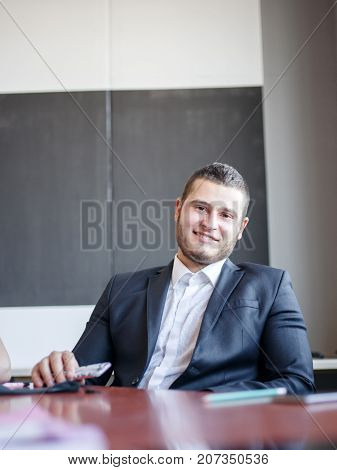 Handsome young boss with beard smiling and posing on camera for working project in formal suit. Business concept.