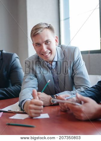 Funny blond man laughs and talking with friend at work at a conference in the office. Business concept.