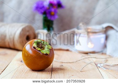 Chocolate persimmon korolek on a wooden table in a rustic style.