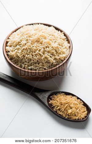 Stock photo of Indian brown wholegrain basmati cooked rice and raw rice, served in a bowl. selective focus
