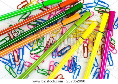 Multicolored Paper Clips And Markers Randomly Scattered On White Paper