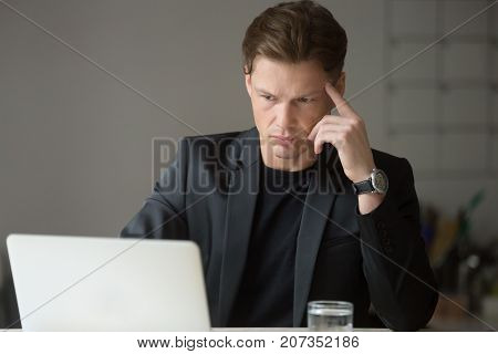 Perplexed or puzzled handsome businessman looking at laptop screen. Thoughtful project manager double checking important financial information, results not making sense. Difficult work task concept.