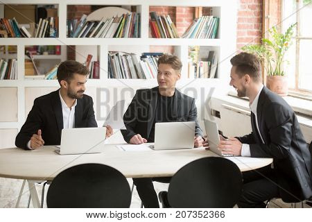 Smiling coworkers discuss positive business matters in front of laptops during briefing. Executives talking about optimistic company goals. Good corporate news, telling jokes, being funny concept.
