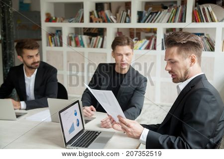 Skeptical boss looking at financial stats report presented by employee. Manager not sure if results are satisfying, confident coworker trying to convince him statistics are going to be successful.