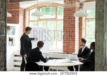 CEO consulting business team about new workflow during briefing. Project manager pointing at chart on board. Employees carefully listen to male executive, looking at graph. Corporate meeting concept.