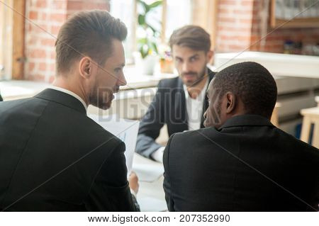 Rear view of serious boss holding financial stats report and scolding african-american employee during briefing because of unproductive results. Company worker being told off for unproductive work.