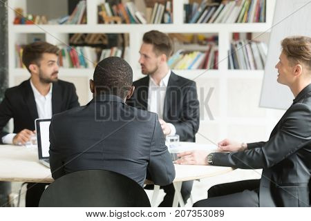 Multiethnic team of male coworkers discussing corporate plans during briefing. Businessmen having discussion about investment opportunities, new business project, company goals to improve workflow.