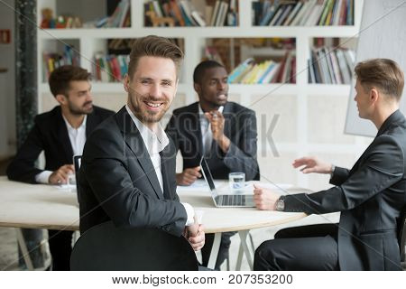 Handsome young smiling businessman looks at camera during business meeting. Team of male corporate colleagues on background, Friendly male executive, successful company representative, CEO or manager.