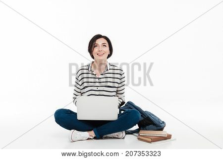 Portrait of a happy teenage girl with backpack holding laptop computer while sitting and looking up isolated over white background
