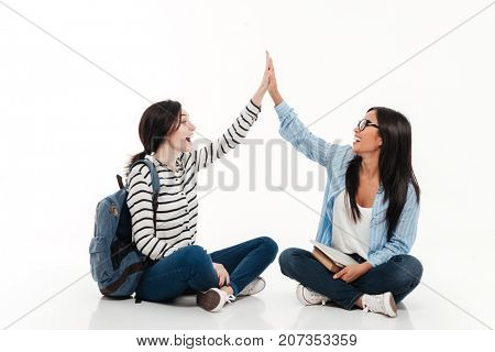 Two multiethnic happy female teenage students sitting on the floor and giving high five isolated over white background
