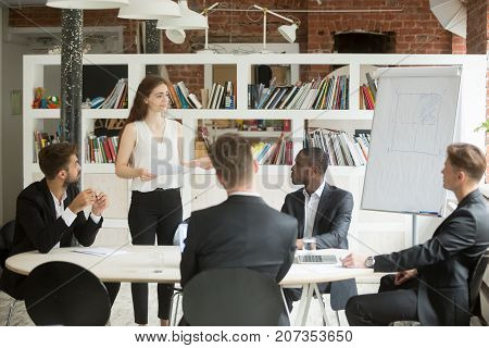 Female executive holding documents, coaching group of corporate employees at briefing. Lady boss consulting colleagues about new workflow plan. Team listening to CEO instructions at business meeting.