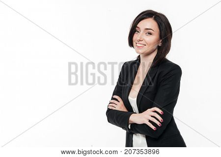 Portrait of a smiling cheerful businesswoman in a suit posing while standing with arms folded and laughing isolated over white background