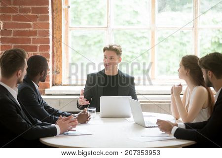 Young serious boss consulting group of employees during briefing meeting. Executive employee talking about company goals to team of multiethnic coworkers. Manager sharing important corporate news.