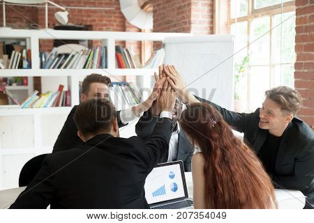 Motivated team of coworkers giving each other high fives, celebrating corporate growth. Pie chart and graph with rising profit stats on laptop screen. Successful teamwork, financial success concept.