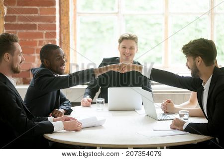 Two positive multiethnic coworkers give each other fist bump celebrating great idea about business project. Team of colleagues in meeting, collaborating on corporate plan. Coworking and teamwork.