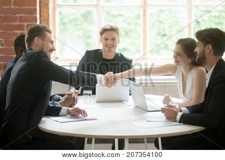 Corporate coworker meeting. Male executive shaking hands with female coworker. Employees greeting and introducing before briefing starts. Team member introduction, teamwork and collaboration concept.
