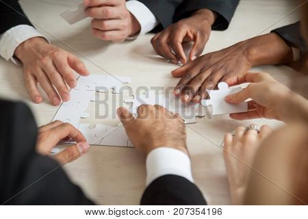 Close up of multiethnic team solving blank puzzle on table. Hands of multi-racial executive employees solving work related problem using game. Team of businessmen brainstorm about corporate solution.