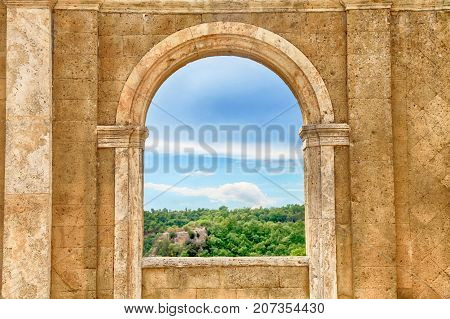 Italian view through the arch window, Tuscany, Italy. Medieval wall with arch window in Italy