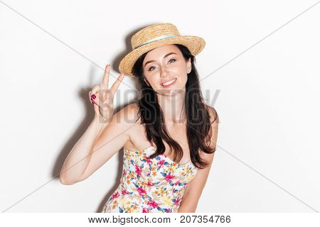 Smiling brunette woman in dress and hat showing peace sign and looking at the camera over white background