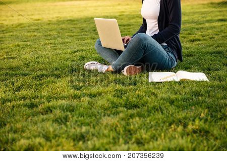 Cropped image of a girl student preparing for exams on laptop computer while sitting on the grass with a textbook