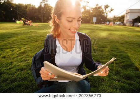 Close up portrait of a casual smiling student girl with backpack holding textbook while sitting on the grass at park