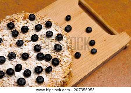 layered cake decorated with berries  blueberry and crumb lies on a wooden board