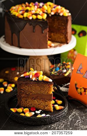 Halloween chocolate cake slice with candy corn and sprinkles on top and other holiday treats