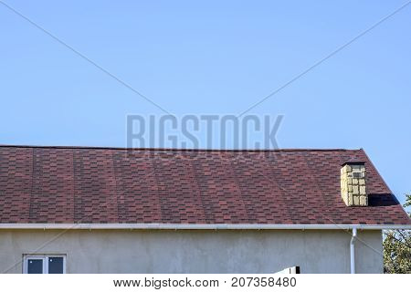 Roof From Multi-colored Bituminous Shingles. Patterned Bitumen Shingles. Bituminous Burgundy Roof.