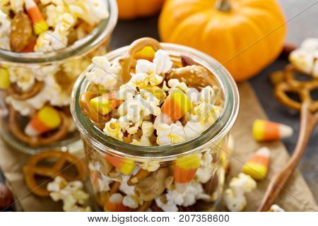 Homemade Halloween trail or snack mix with candycorn, popcorn, pretzels and nuts in glass jars