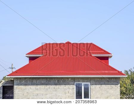 Red Corrugated Roof. House Of Cinder Block. House With Plastic Windows And Roof Of Corrugated Sheet
