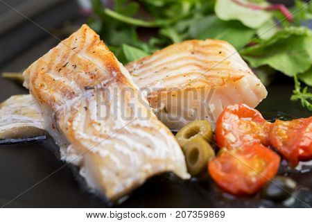 Cod fillets with olives and capers on black plate / Mediterranean cuisine