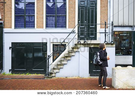 AMSTERDAM NETHERLANDS - JUNE 21 2016: A house in Amsterdam with a green door and a tourist right on the side of Anne Frank's Museum. Amsterdam Netherlands.