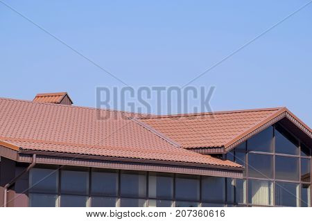 A Building With A Red-brown Roof. Modern Materials Of Finish And Roofing