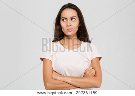 Portrait of an upset unsatisfied asian woman standing with arms folded and looking away isolated over white background
