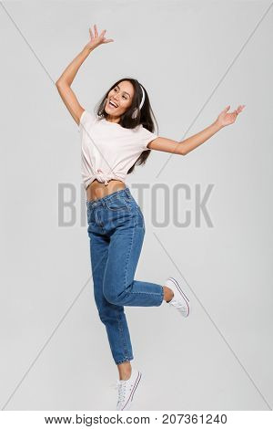 Full length portrait of a happy joyful asian woman in headphones listening to music and dancing isolated over white background