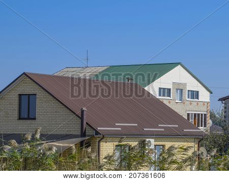 Houses With Corrugated Metal Roofs. Brown And Green Roof. Modern Materials For Roofing.