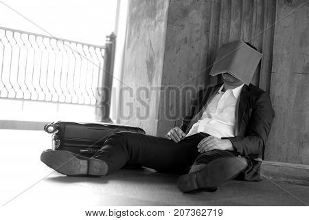 Stressed Asian Businessman Bankrupt With Sitting At Outdoor And Book Close Face.
