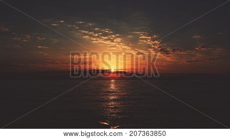 Stunning orange sunset over the sea during deep evening: rare clouds calm water with small waves sun and specular from it on the water slightly visible godrays panoramic view