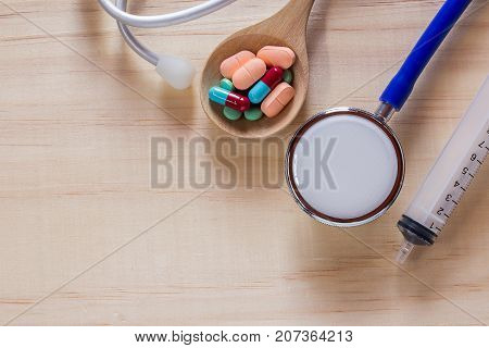 Syringeblue stethoscope and pills with tablets on wooden table top view with copy space. Health and medical concept