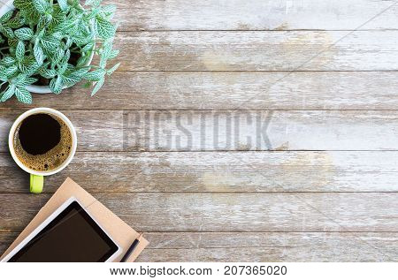 Office desk table- Blank paper notebook with pencil and cup of coffee on wooden table.View from above.Office supplies and gadgets on desk table.Working desk table concept.Writing notes.