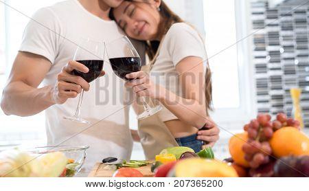 Young asian man and woman couple together holding wine glasses drinking after dinner in kitchen room at home lover romantic concept