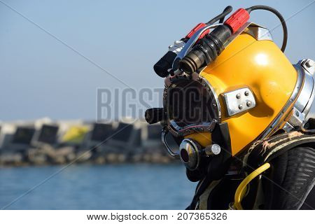 commercial diver ready for the dive in deep water in the mediterranean sea using diving helmet and umbilical