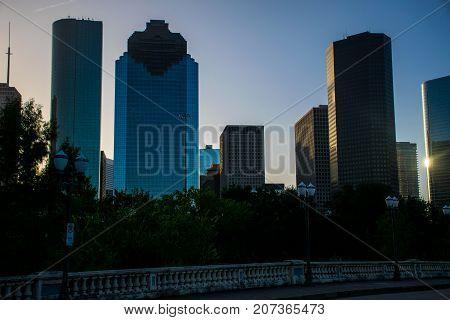 Houston Texas Sunrise Colors off modern Tall Huge Skyscrapers along Houston , Texas downtown Cityscape standing on Sabine Street Bridge