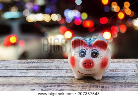 Piggy bank on wooden table over blurred bokeh light background. saving money and business concept.