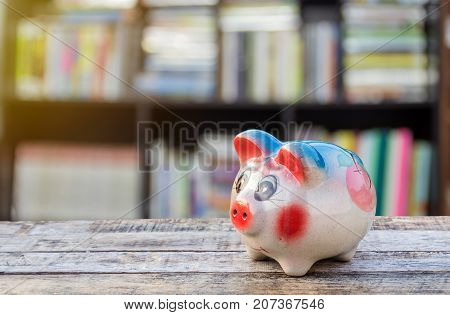 Piggy bank with morning sunlight on wooden table over blurred background. saving money concept.